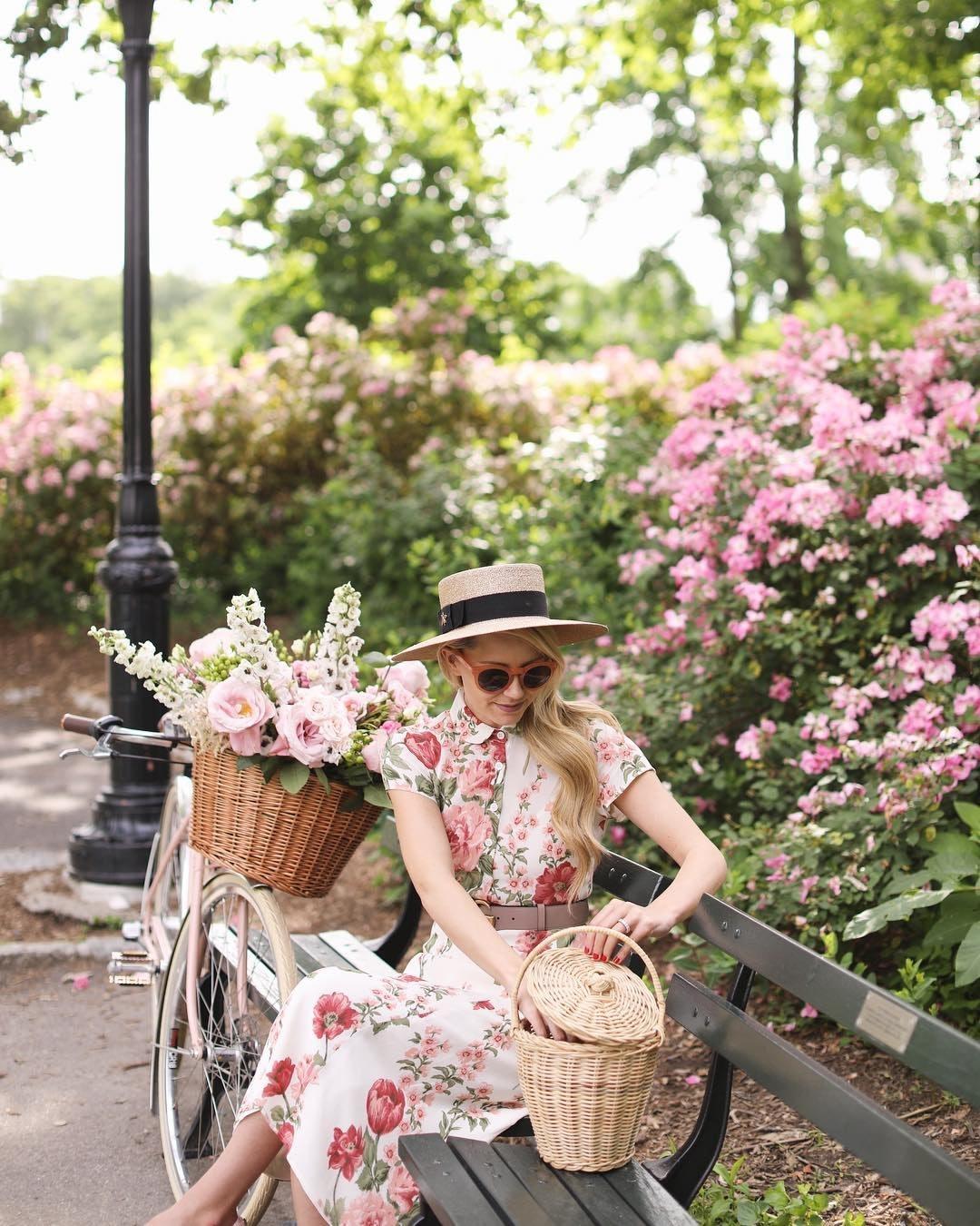 Frühlingshaftes Stimmungbild mit einer Frau mit Sonnebrille und Hut, die auf einer Parkbank sitzt. Ihr Fahrrad lehnt an der Bank und im geflochtenen Fahrradkorb ist ein prächtiger Blumenstrauß.