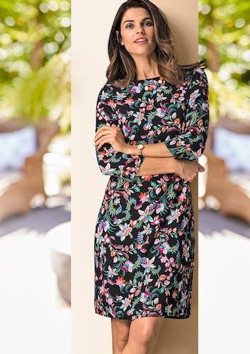 Frau mit braunen Haaren lehnt an einer Säule und trägt ein schwarzes Kleid mit tropischem Blumenmuster und eine Uhr.