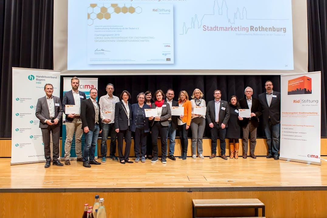 Die Gewinner der Coaching-Programme 2019 aus Murnau, Gemünden, Friedberg, Erding, Rothenburg ob der Tauber und Obernburg zusammen mit dem Handelsverband Bayern, der CIMA und der Rid Stiftung.