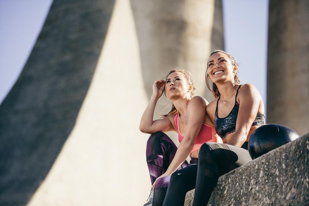 Sportliche junge Frauen sitzen auf Mauer