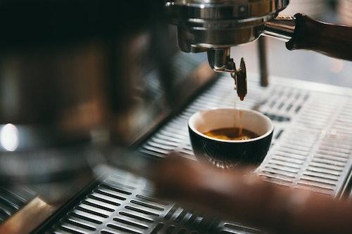 Het espresso som droppar ned i en espressokopp från en italiensk kaffemaskin.