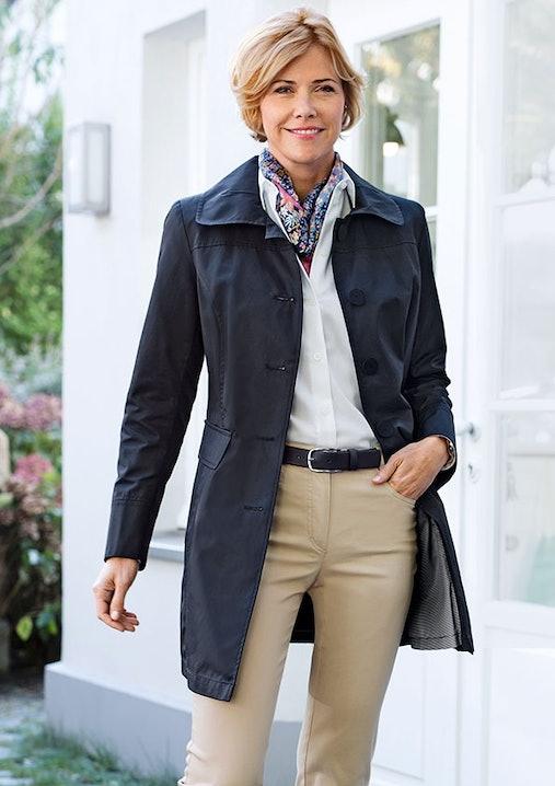 Blonde Frau steht vor einer weißen Häuserwand. Sie trägt schwarzen Mantel, weiße Bluse, gemusterten Schal und eine beige Hose.