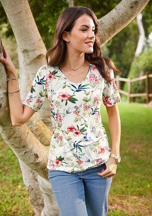 Frau in weißem T-Shirt mit Blumenmuster und Jeans lehnt mit einem Arm an einem Baum.