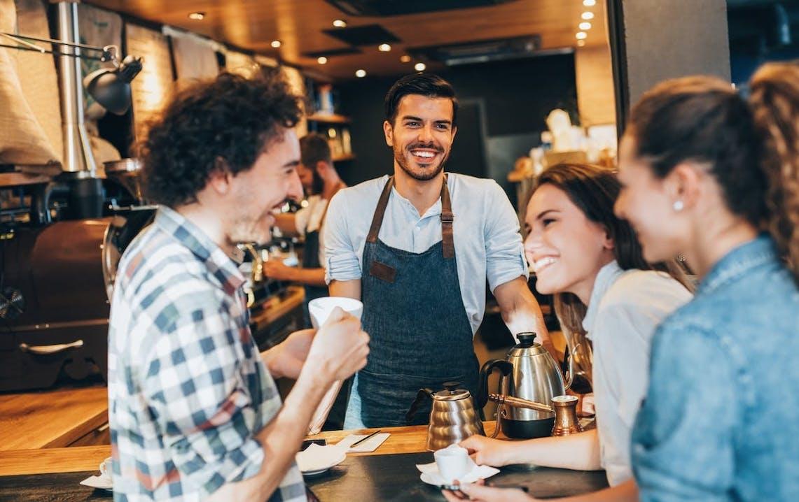 Mies ja kaksi naista nauttivat espressojaan kahvilan tiskillä baristan seurassa.