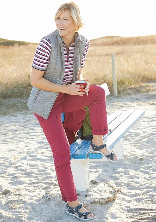 Frau mit Weste sitzt auf einer Bank am Strand und hält eine rote Tasse in der Hand.
