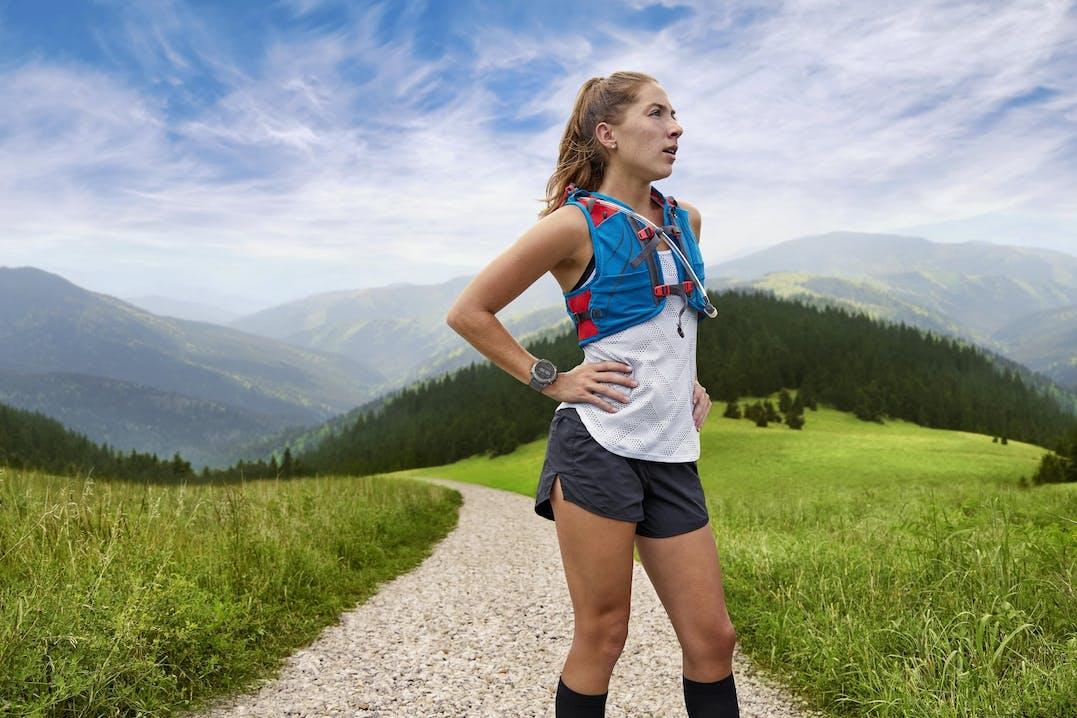 Läuferin, stehend, in den Bergen, mit Garmin Enduro Sportuhr