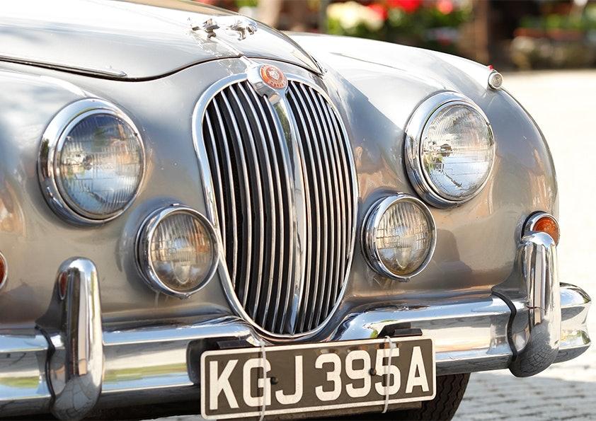 Front eines silbernen Oldtimers von Jaguar mit Nummernschild.