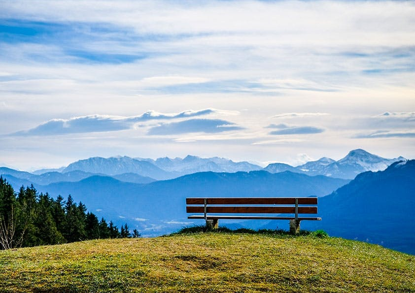 Holzbank auf einem Hügel. Im Hintergrund Wald, Berge und Wolken.