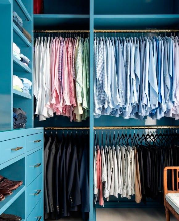 Blauer Kleiderschrank mit nach Farben sortierte Hemden und Hosen.