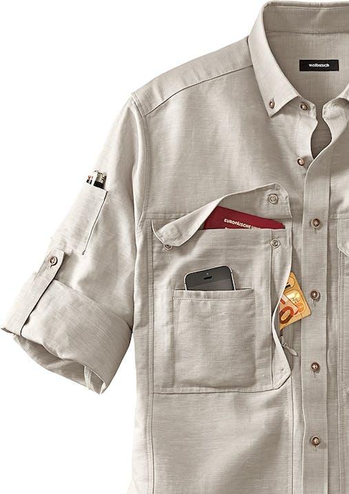 Anschnitt eines beigen Hemdes mit hochgeknöpftem Ärmel, Knopfleiste und Stifttasche am Ärmel. In der Brusttasche stecken ein Reisepass, Smartphone und ein Geldschein.