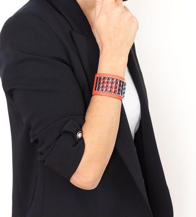 Large bracelet manchette en cuir de couleur rouge orangé orné de ses perles de verre vrillées. Une alternance de longues perles de couleur grise métallisée et noire apporte brillance à cette manchette cuir (couture à la main). Chaque perle tube est encadrée de petites perles en acier inoxydable. Cuir doublé d'un cuir naturel au tannage végétal (sans traitement chimique tel que le chrome ni teinture). 2 tailles d'attache grâce aux boutons pression : 16 cm et 17,5 cm. Ce bracelet conviendra à des poignets jusqu'à 17 cm. Les boutons pression sont en acier inoxydable de qualité 316 afin de vous ga