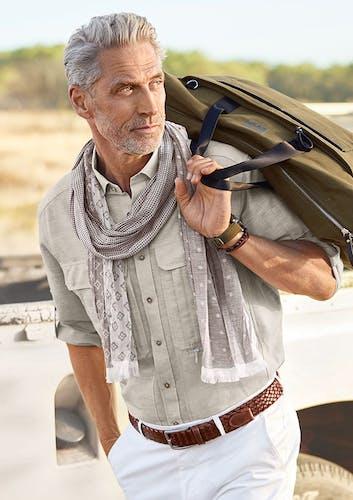Mann mit grauen Haaren und Bart trägt ein olivfarbenes Hemd, eine weiße Hose, einen braunen Gürtel und einen leichten Schal. Er trägt eine Reisetasche über der Schulter.