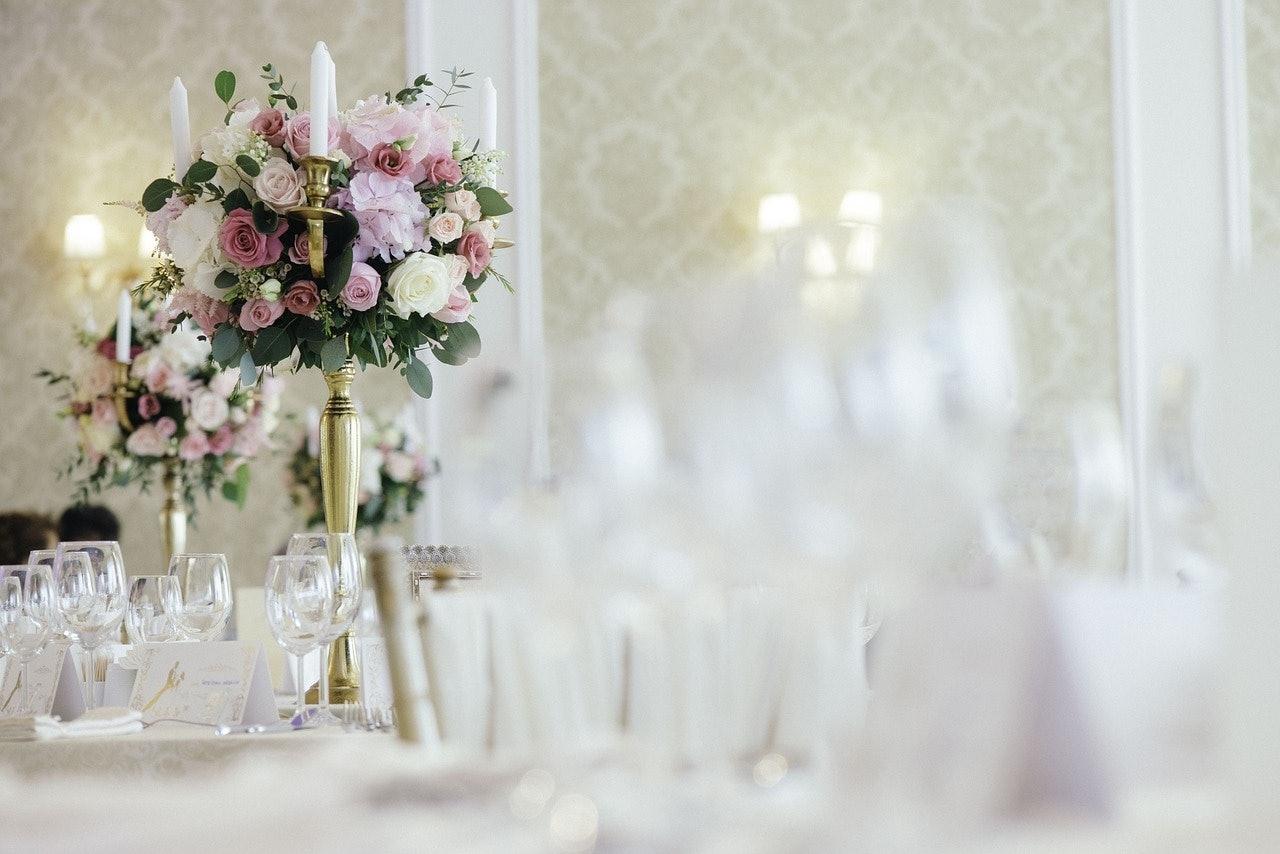 Königlische Hochzeitsdeko mit weißen Kerzen und Rosensträußen in verschiedenen Rosatönen dazu goldene Kerzenhalter.