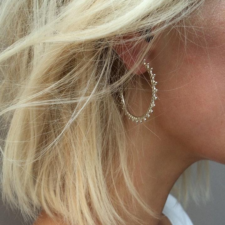 Petites créoles en argent composées d'un motif trois perles.    3,4 cm de diamètre.    Depuis sa première collection en 2010, Agnès de Verneuil puise l'inspiration dans tout ce qu'elle découvre au fil de ses voyages et fait de chacun de ses bijoux un trésor d'élégance et de raffinement.    Ne pas exposer à l'eau.  Nettoyer avec un chiffon doux. Matière principale : Argent 925/1000