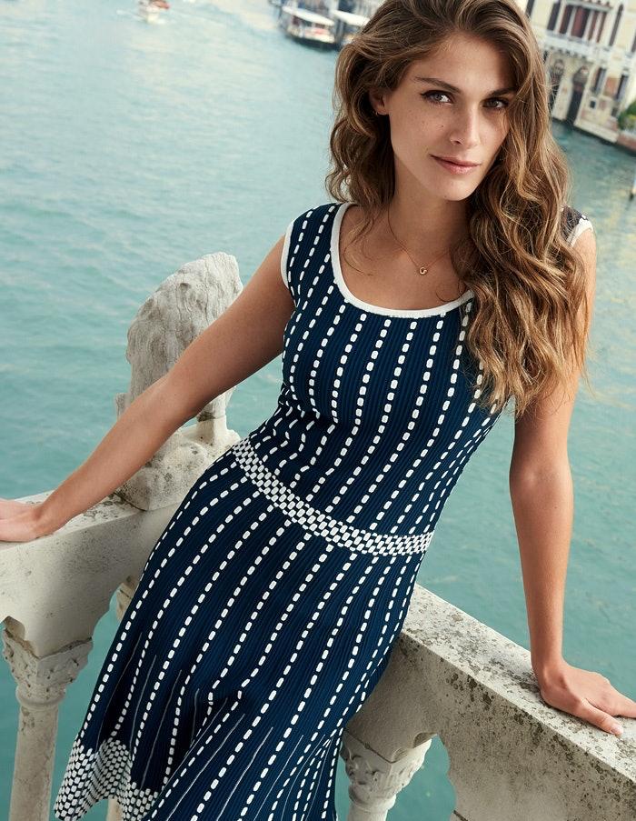 Elisa Sednaoui in einem blau weißen Kleid vor türkisblauem Wasser in Venedig..