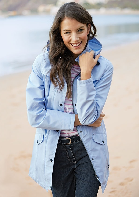 Lachende Frau mit braunen, langen Haaren trägt eine hellblaue Jacke, Shirt und Jeans. Im Hintergrund sieht man Strand und Meer.