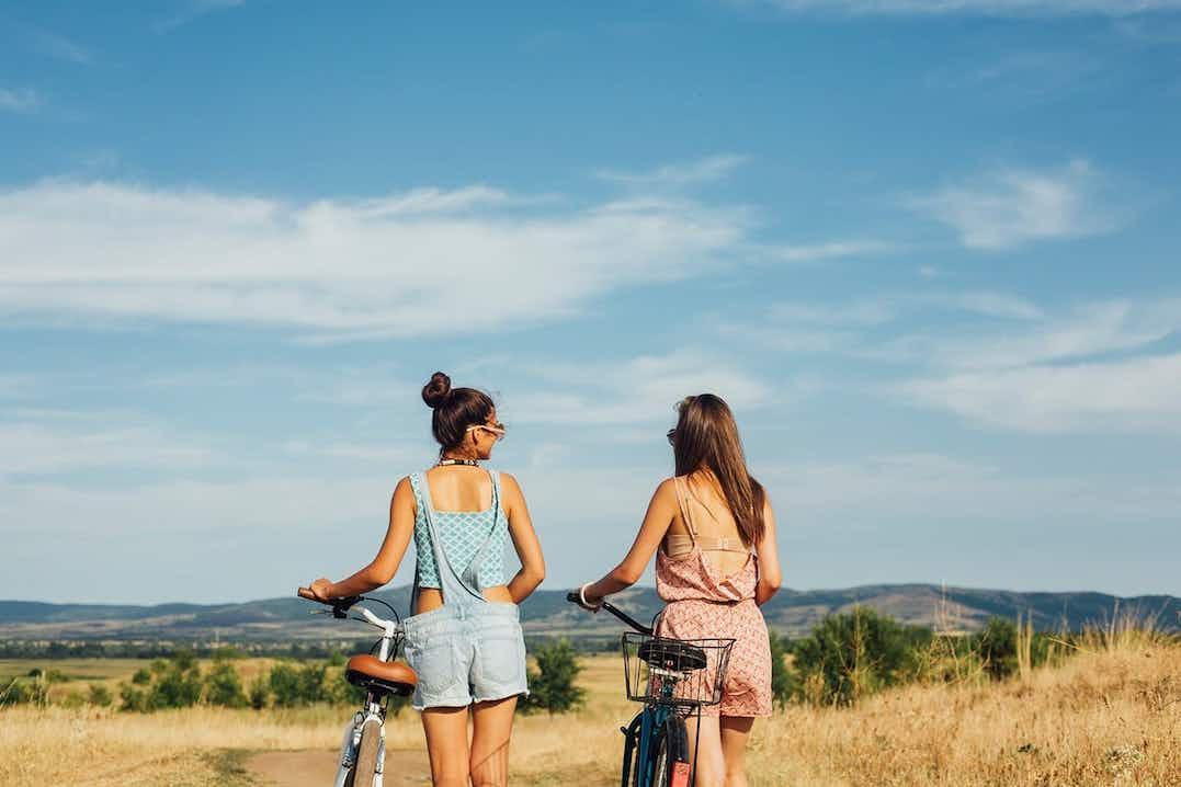 Kaksi päivettynyttä naista työntää polkupyöriään niityn reunalla. Toisella on yllään kesäinen farkkuhaalari ja toisella haalariasu.