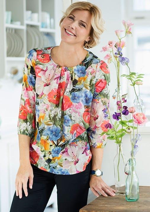 Frau mit kurzen blonden Haaren lächelt und trägt eine Bluse mit Blumenmuster.