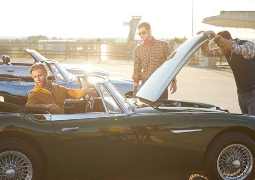 Drei Männer stehen vor Oldtimer mit offener Motorhaube