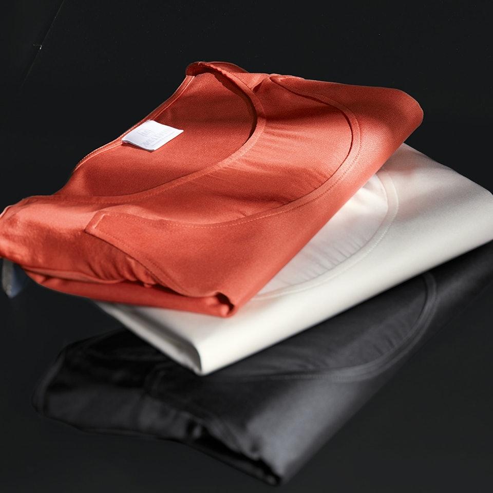 Kleierstapel aus Shirts in Orange, Wollweiß und Anthrazit.