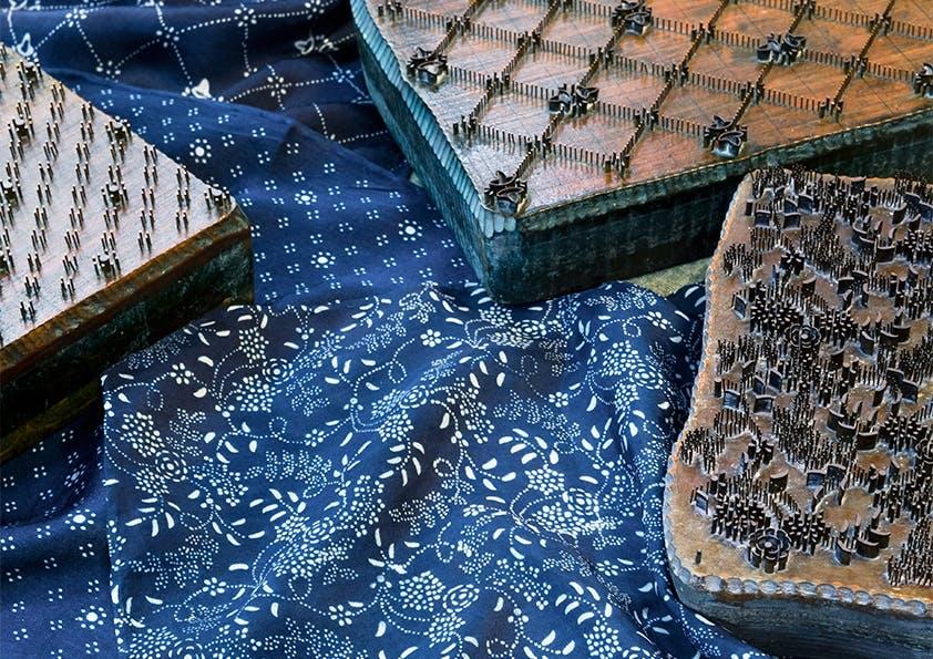 Blauer Stoff mit weißen Ornamenten und braune Stempel.