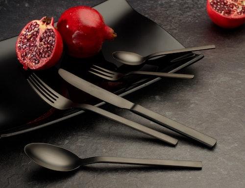 Schwarzes Besteck und Granatapfel auf schwarzem Teller