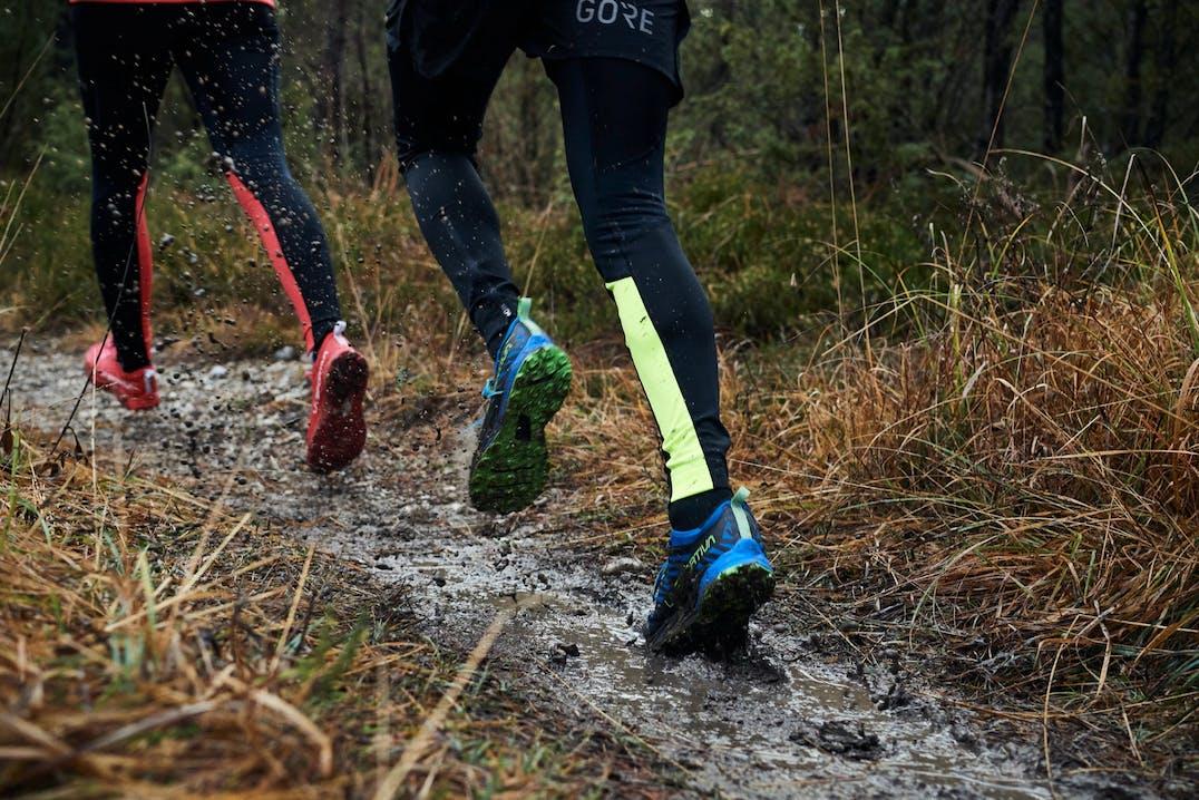 Persone che corrono in mezzo al fango