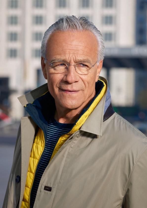 Nahaufnahme von einem Mann mit Brille und grauen Haaren.