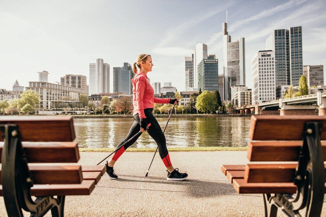 Donna che cammina in ambiente urbano con bastoncini