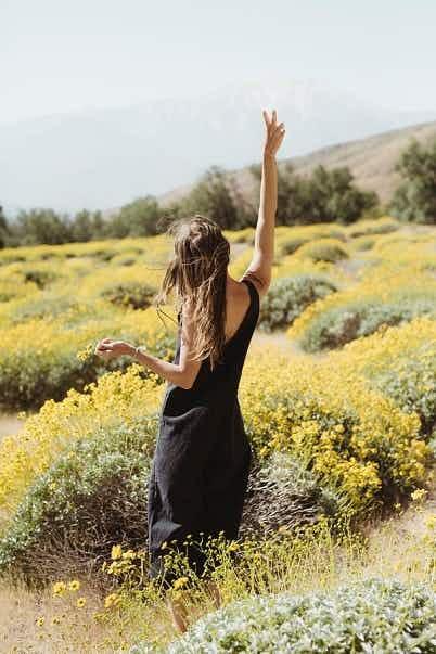 Villiniityllä seisova nainen on kohottanut käsivartensa ja näyttää rauhanmerkkiä
