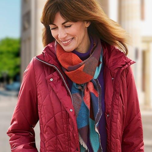 Braunhaarige Frau trägt eine rote Steppjacke und einen bunten Schal und lächelt.
