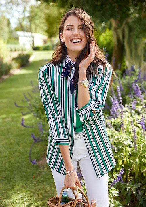 Lachende Frau vor einer grünen Wiese. Sie trägt eine gestreifte Bluse, eine weiße Hose, ein grünes Shirt und ein Tuch.