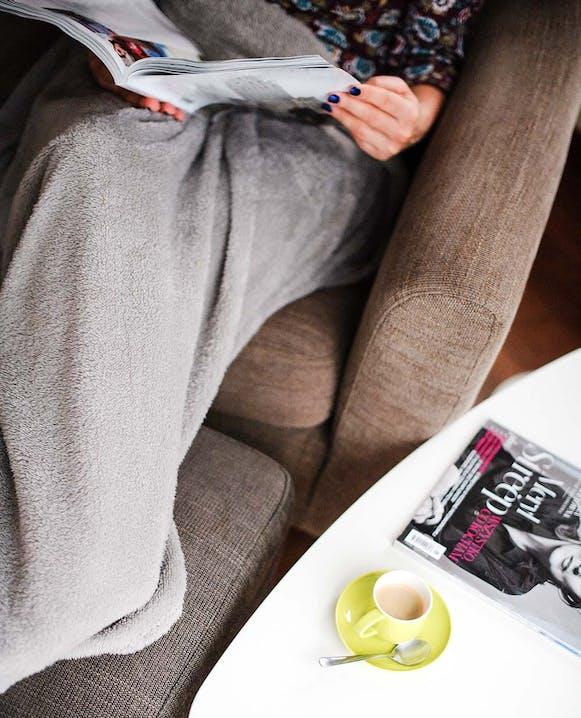 Frau liest Magazin auf dem Sofa als Ausgleich zum Sport