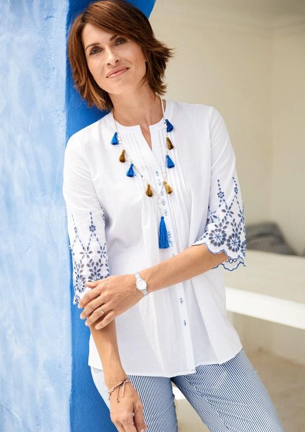 Frau mit weißer Tunika mit blauen Ärmeln und einer langen Kette lehnt an einer blauen Wand.